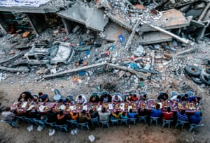 Palestinian families break their fast next to a building in the Gaza Strip destroyed in a recent confrontation between Hamas and Israel during the Muslim holy fasting month of Ramadan