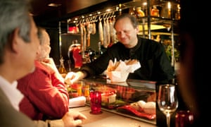 Joël Robuchon with guests at L'Atelier de Joël Robuchon in Paris, France, which he opened in 2003, inspired by a demand for great food in less formal surroundings.