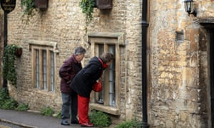 Visitors look in the window of a house in Castle Combe, Wiltshire