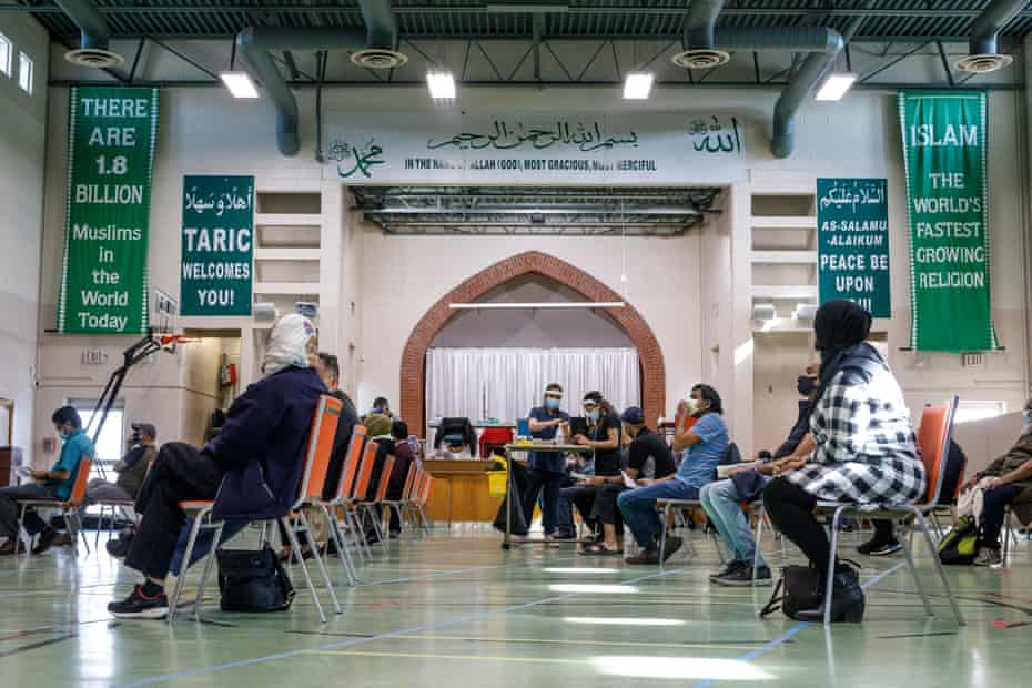 People wait as healthcare workers from Humber River hospital administer Moderna vaccines at the Toronto and Region Islamic Centre congregation.