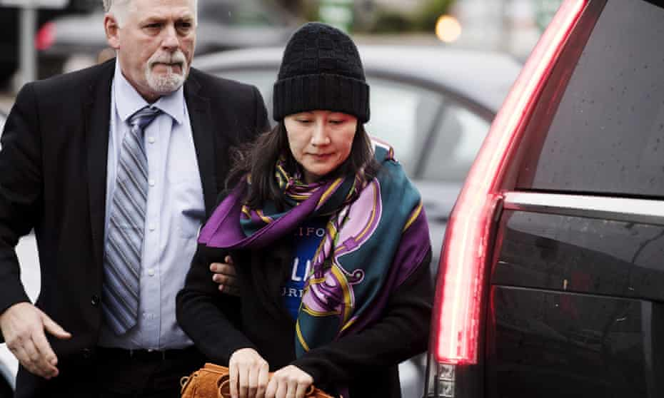 Huawei's chief financial officer, Meng Wanzhou, arriving at a parole office with a security guard in Vancouver, British Columbia, on Wednesday