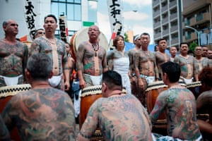 Participants pose to show their traditional Japanese tattoos