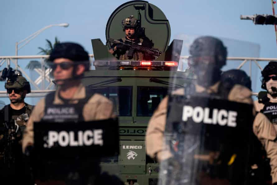 A Miami Police officer watches protesters from an armoured vehicle.