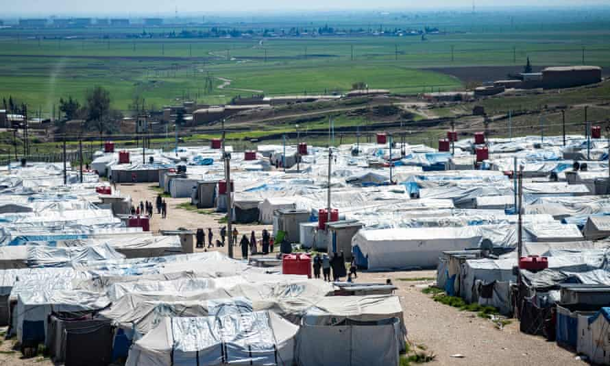 Women and children walk at Camp Roj walk between temporary white dwellings