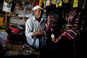 Cassim Juma Vuai, 71, serves a customer in his shop in the town of Uroa