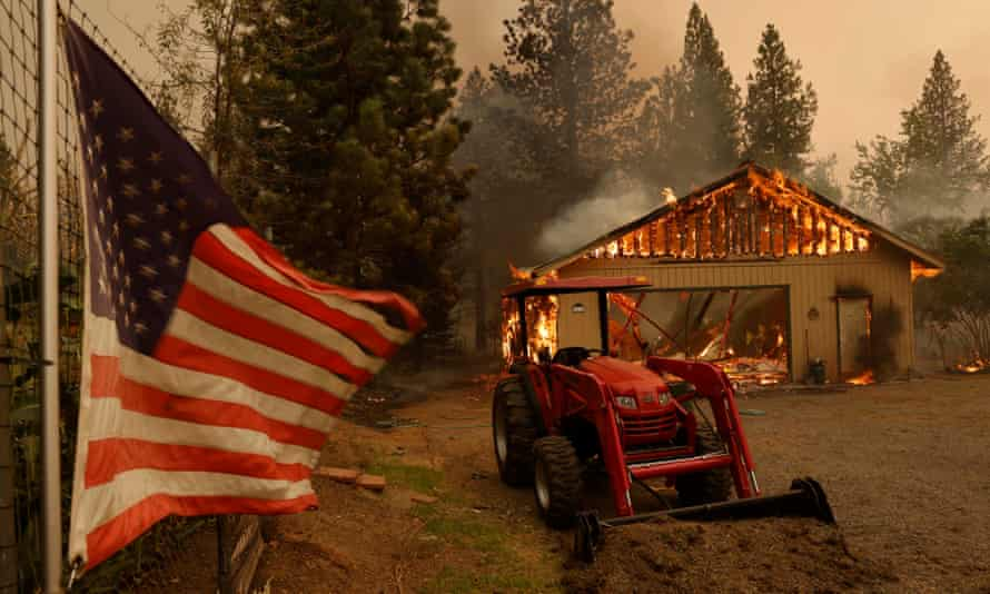 A structure is engulfed in flames from the Dixie fire near Taylorsville, California Friday.