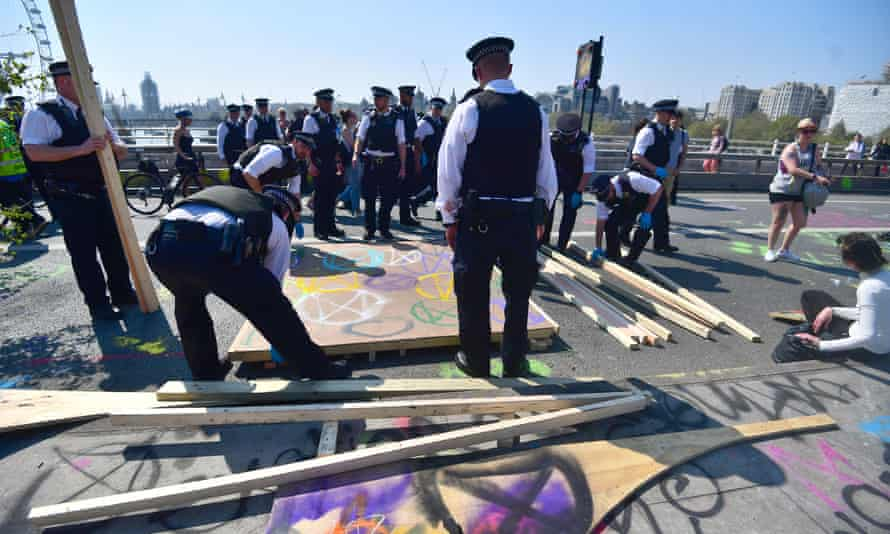 Police dismantle the skate ramp erected by Extinction Rebellion demonstrators on Waterloo Bridge in London.