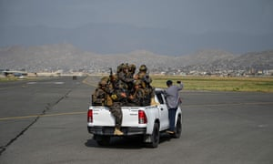 Members of the Taliban Badri 313 military unit ride a vehicle on the runway of the airport in Kabul on August 31.