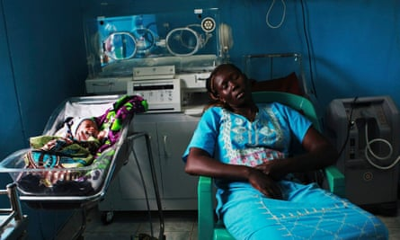 A woman sleeps next to her newborn baby in a nursery in the Juba Teaching Hospital