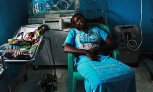 A woman sleeps next to her newborn baby in a nursery in the Juba Teaching Hospital, South Sudan