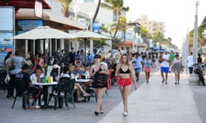 People are seen walking on the Hollywood Beach Boardwalk in Florida, USA on 26 June, 2020 as Florida reports another record spike in coronavirus cases.