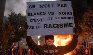 Демонстрант держит баннер перед горящей баррикадой после вмешательства сил безопасности в знак протеста против жестокости полиции в здании суда