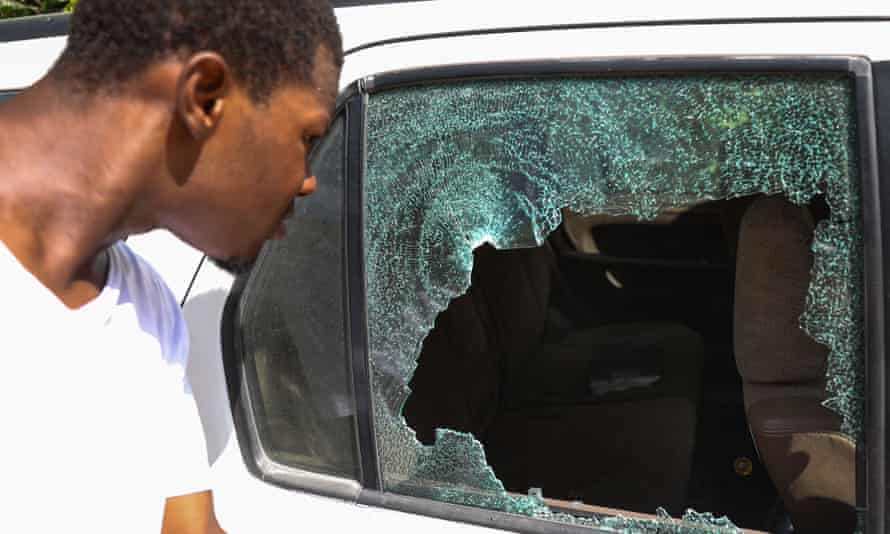 A man looks at bullet holes in a car outside the presidential residence in Port-au-Prince