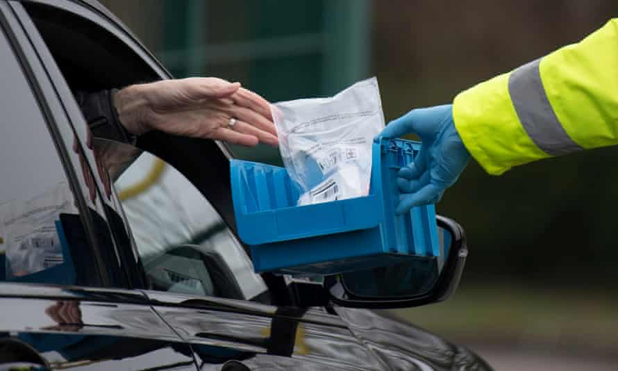 A coronavirus test is handed through a car window in Stoke Gifford, Gloucestershire
