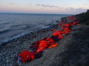 An orange rind of lifejackets, visible from the air, lines the fatal rocks of Lesbos