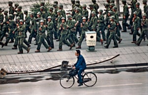 A cyclist passes troops after the declaration of martial law