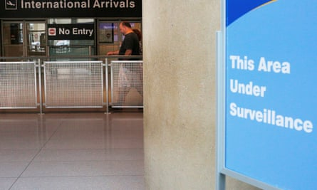 A sign warns of surveillance at the international arrival area, on the day that Donald Trump's limited travel ban took effect.