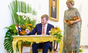 King Willem-Alexander seated at a desk and Queen Maxima looking on at the president's Bogor Palace
