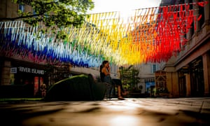 A person sits beneath rainbow coloured street decorations on a sunny morning