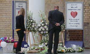 Commuters look at floral tributes placed at Manchester Victoria railway station, which reopened on Tuesday.