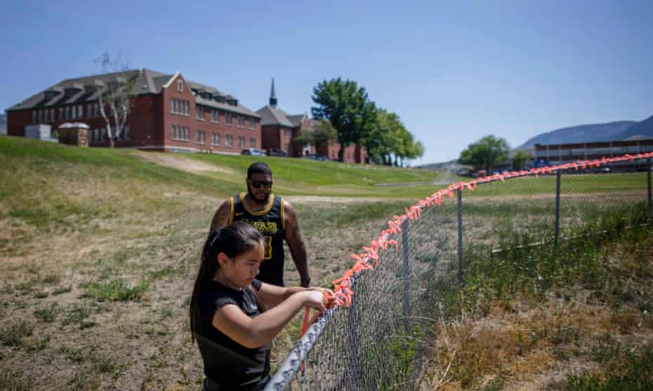 Autumn Peters places 215 ribbons on the fence behind the former Kamloops Indian residential school this week, in honor of the 215 children whose remains have been discovered buried near the facility, as well as her grandfather Clayton Peter, a survivor of the school, and all other survivors.