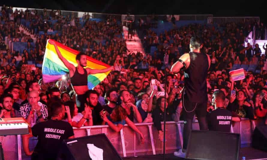 A fan of holds a rainbow flag during Mashrou' Leila's concert at the 2017 Ehdeniyat International festival in Lebanon.