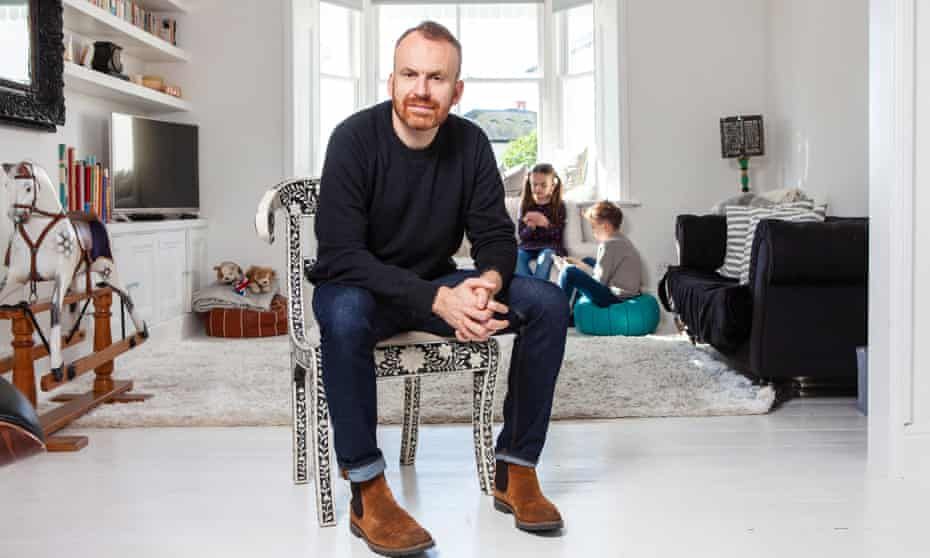 Matt Haig sitting on a chair in his living room, his two young children playing at the back of the room