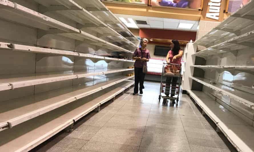People walk past empty shelves at a supermarket in Caracas in January.