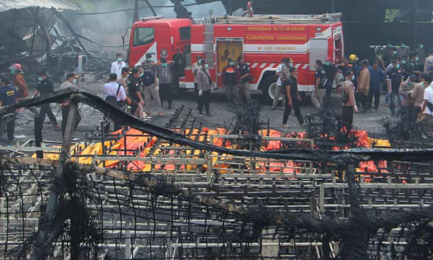 Indonesian forensic officers comb through the ashes and debris at the factory near Jakarta.