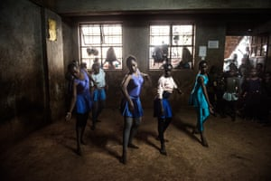 Some of the older girls practise a group dance as onlookers watch them