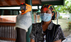 A woman's temperature is checked in Kokopo, East New Britain province, Papua New Guinea.