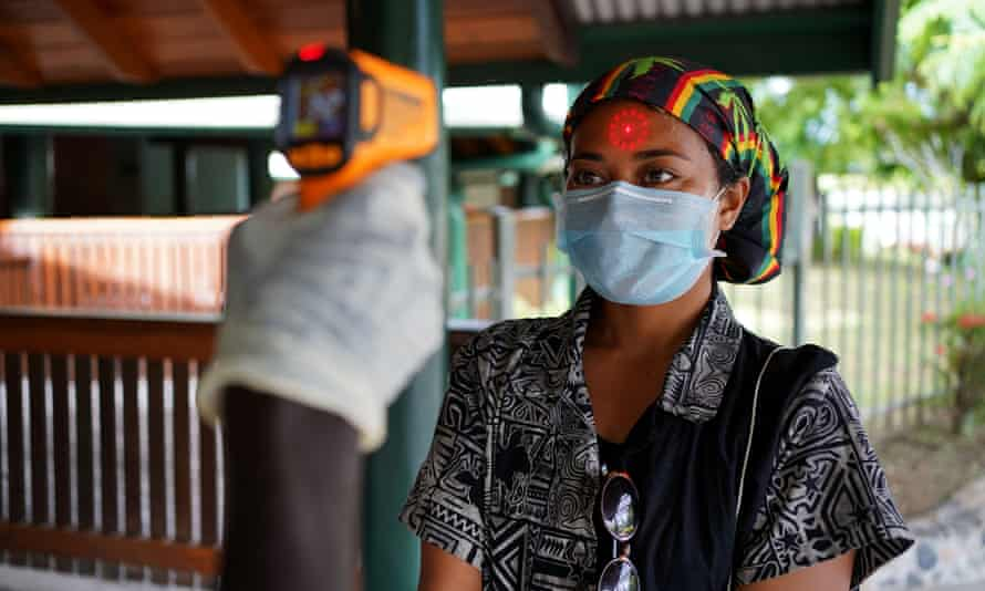 A woman's temperature is checked in Papua New Guinea