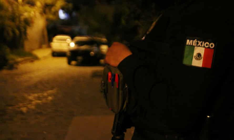 A police officer guards a crime scene in Tlaquepaque, Jalisco, Mexico, on 8 July.