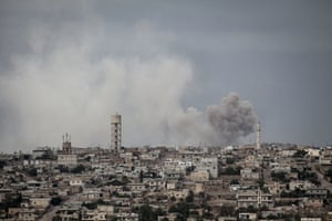 Smoke rises after a bomb hit on a village in Idlib province