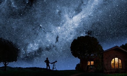 A man gazes at the Milky Way outside his house at night.