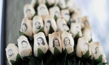 White roses with the faces of victims of the Sandy Hook Elementary School shooting. The guns and ammunition used were legally purchased the gunman Adam Lanza's mother.