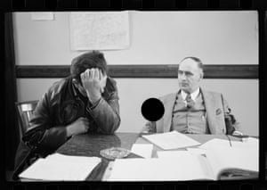 Two men at desk, one with head in his hands
