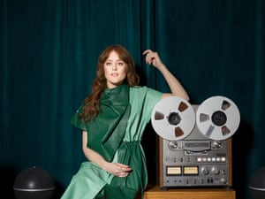 Hannah Peel in striking green dress next to old-fashioned reel to reel tape player
