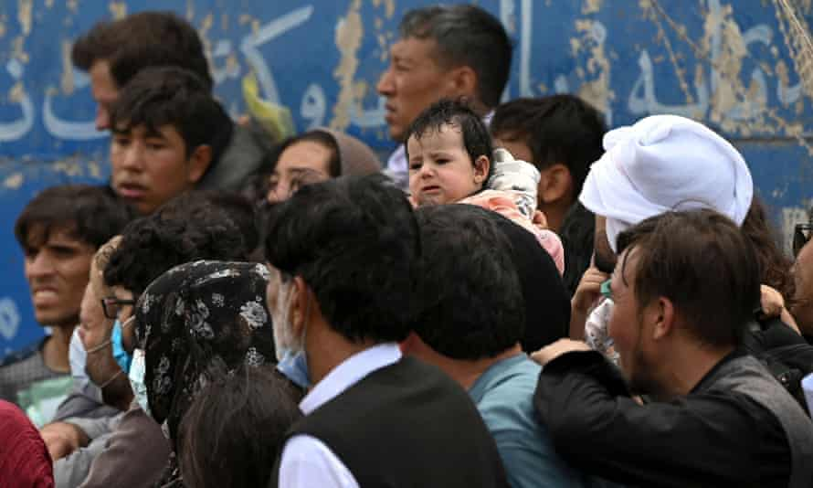 Afghans gather on a roadside near the military area of the airport in Kabul, hoping to flee from the country