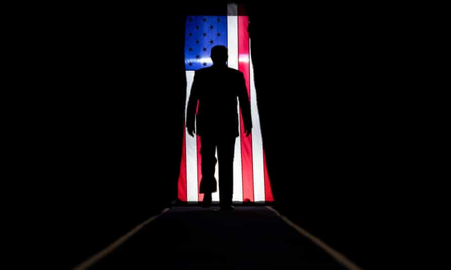 Donald Trump silhouetted against a US flag