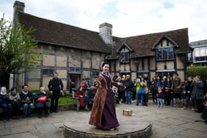 Tourists watch an actor perform at the house where Shakespeare was born