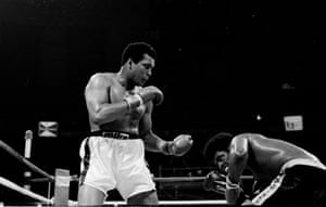 Spinks ducks low as Muhammad Ali lands a left during their heavyweight title bout at the Superdome in New Orleans.
