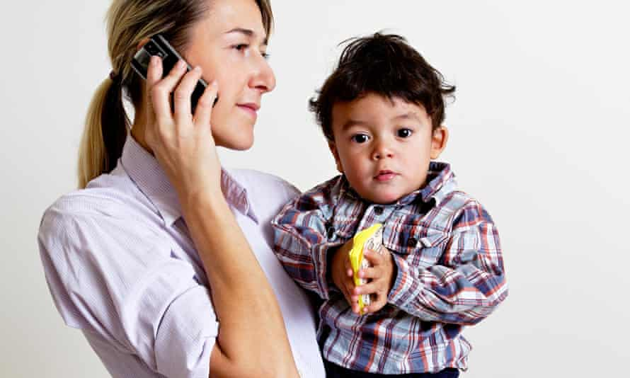 mother holding child and talking on mobile phone
