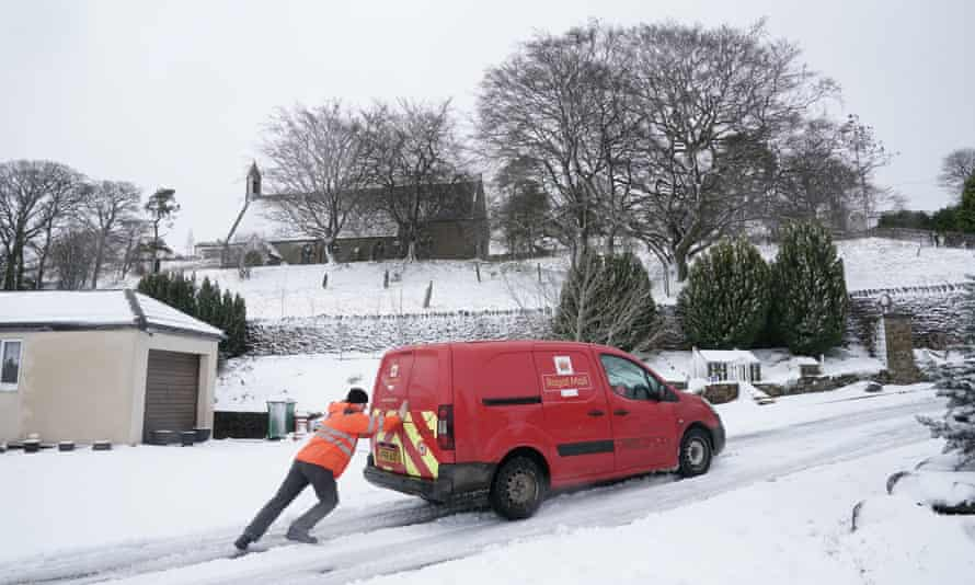 A Royal Mail worker attempts to push a delivery van up a snow-covered road in Nenthead, Cumbria