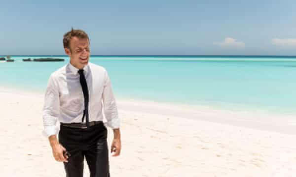 French president Emmanuel Macron walks along a beach.