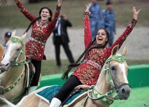 Riders in traditional dress perform stunts on horseback at the opening ceremony