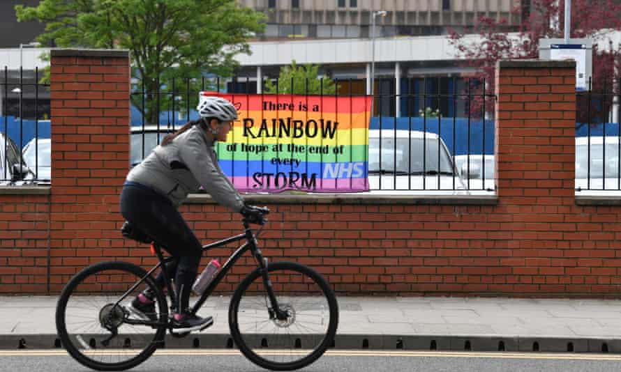 A cyclist passes a rainbow banner outside Salford Royal Hospital last week.
