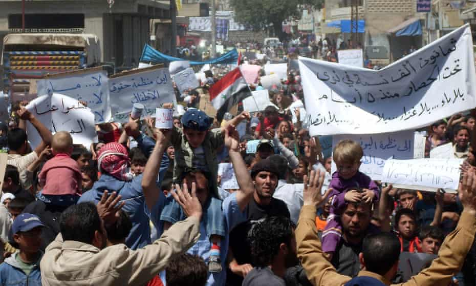 Syrian anti-government protesters hold banners in April 2011