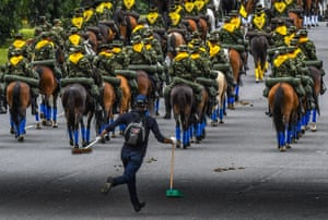A cleaner runs behind mounted soldiers during an independence day parade in Bogotá, Colombia