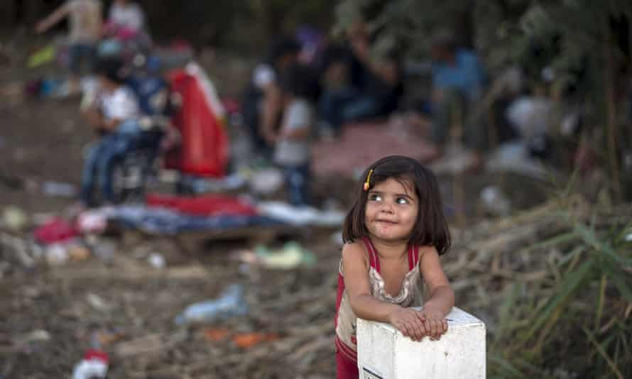 A Syrian girl leans on a border stone on the Serbian border with Hungary